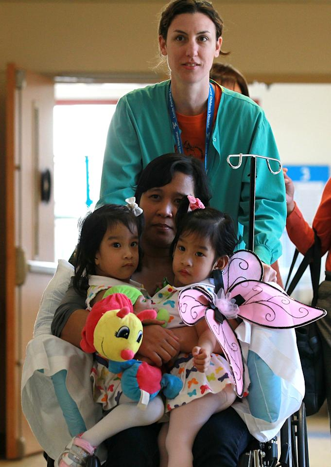 PALO ALTO, CA - OCTOBER 31:  Conjoined twins Angelica (L) and Angelina Sabuco (R) ride on a wheelchair with their mother Ginady (C) before a press conference at the Lucile Packard Children's Hospital at Stanford on October 31, 2011 in Palo Alto, California.  Two year-old conjoined twins Angelica and Angelina Subaco who are connected at the chest and abdomen are preparing for separation surgery by Dr. Gary Hartman. The surgery will last between 6 and 8 hours that is followed by three hours of reconstructive surgery for each girl.  (Photo by Justin Sullivan/Getty Images)