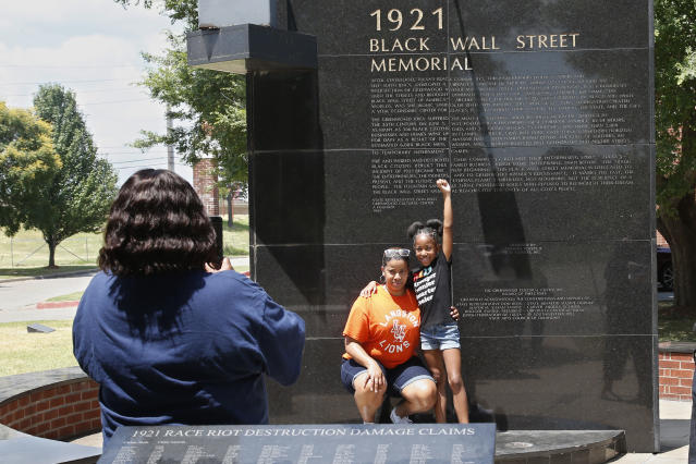 Katrina Cotton, center, of Houston, poses for a photo with her daughter, Kennedy Cotton, age seven, as her aunt, Janet Wilson, left, takes the photo, at the Black Wall Street memorial in Tulsa, Okla., Monday, June 15, 2020. (AP Photo/Sue Ogrocki)