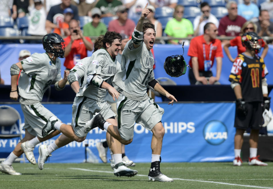 """FILE - In this May 28, 2012, file photo, Loyola lacrosse players, including Greg Catalano, center, rush the field after defeating Maryland 9-3 in the NCAA Division I men's lacrosse championship game in Foxborough, Mass. Loyola Maryland athletic director Donna Woodruff said her position on name, image and likeness compensation has """"evolved a little bit"""" and she is less concerned about its impact on competitive balance. She said at Loyola, where the women's and men's lacrosse teams routinely are ranked among the best in the country, athletes in those sports could get more popular than they might at schools where the football or basketball programs draw most of the attention. (AP Photo/Gretchen Ertl, File)"""