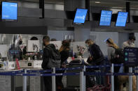 Travelers wearing masks check in at United desks at San Francisco International Airport during the coronavirus outbreak in San Francisco, Tuesday, Nov. 24, 2020. (AP Photo/Jeff Chiu)
