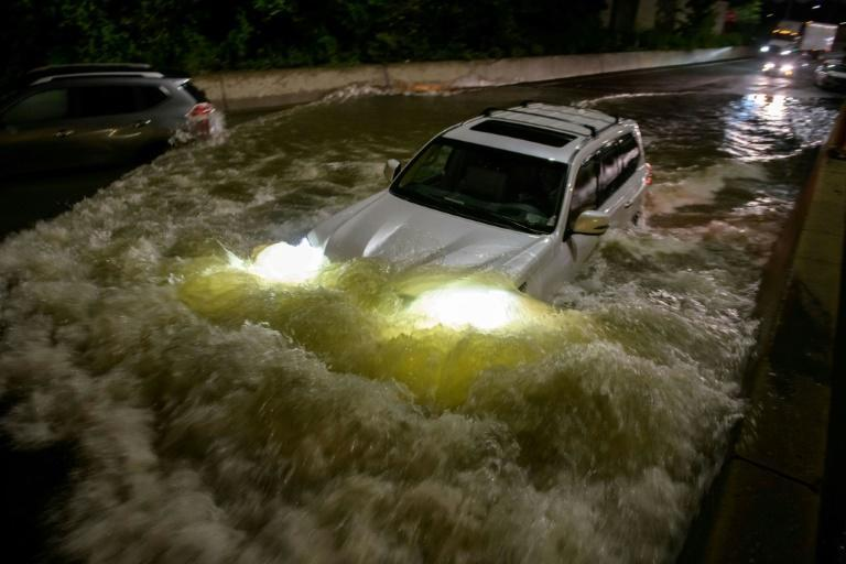 A motorist drives a car through a flooded expressway in Brooklyn, New York early on September 2, 2021, as flash flooding and record-breaking rainfall brought by the remnants of Storm Ida swept through the area (AFP/Ed JONES)