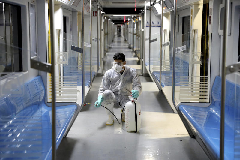 FILE - In this Feb. 26, 2020, file photo, a worker disinfects subway trains against coronavirus in Tehran, Iran. As the coronavirus spreads around the world, International health authorities are hoping countries can learn a few lessons from China, namely, that quarantines can be effective and acting fast is crucial. On the other hand, the question before the world is to what extent it can and wants to replicate China's draconian methods. (AP Photo/Ebrahim Noroozi, File)