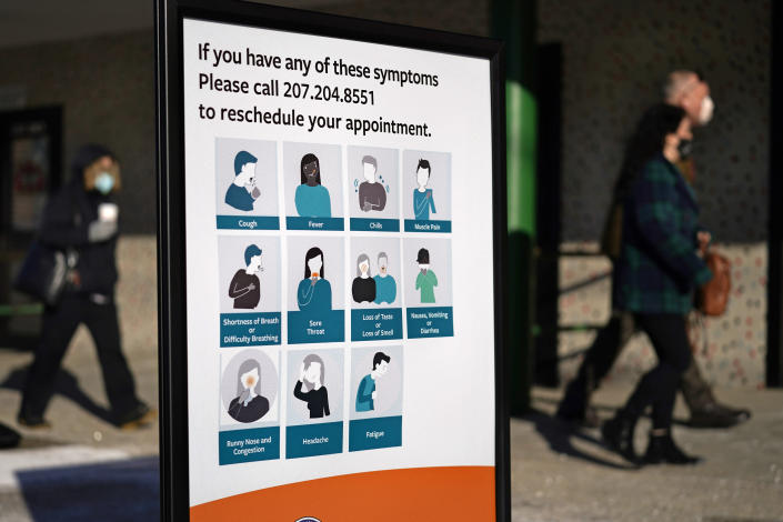 A sign lists symptoms that would require a rescheduled appointment at a COVID-19 mass vaccination site, Tuesday, March 2, 2021, at the Portland Expo in Portland, Maine. (AP Photo/Robert F. Bukaty)