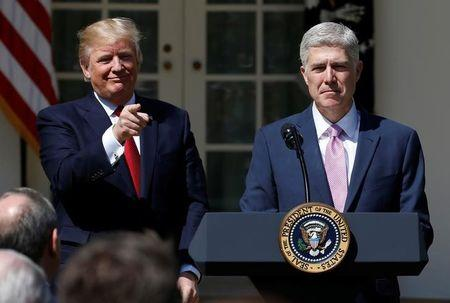 U.S. President Donald Trump points to the audience after the swearing in of Judge Neil Gorsuch as an Associate Supreme Court Justice in the Rose Garden of the White House in Washington, U.S., April 10, 2017.  REUTERS/Joshua Roberts