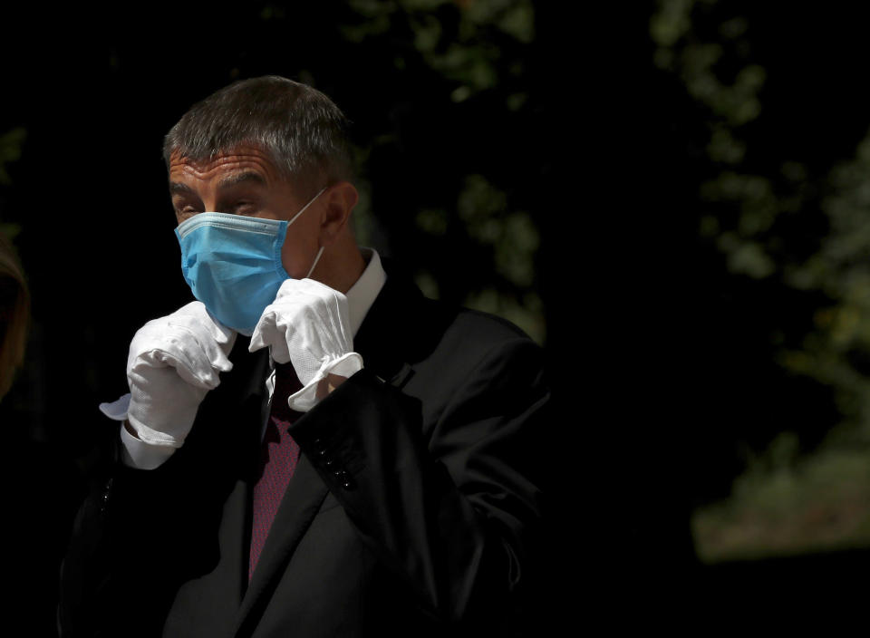 FILE - In this June 3, 2020 file photo Czech Republic's Prime Minister Andrej Babis adjusts his face mask as he waits for the arrival of his Slovak counterpart Igor Matovic in Prague, Czech Republic. (AP Photo/Petr David Josek, File)
