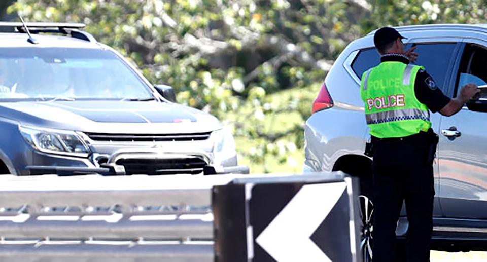 Police officer speaks to a motorist who is entering Queensland from New South Wales through a border checkpoint on the Gold Coast on December 21, 2020.