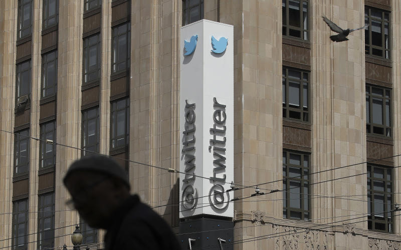 FILE - In this July 9, 2019, file photo a pedestrian walks across the street from the Twitter office building in San Francisco. A complaint unsealed in a federal court detailed a coordinated effort by Saudi officials to recruit employees at the social media giant who could tap into the Twitter accounts of political opponents and access their personal data, including internet protocol addresses that can give up a user's location. (AP Photo/Jeff Chiu, File)