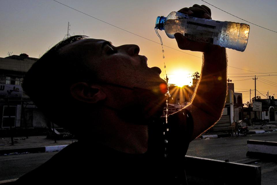 Laith Jabbar, a gas station worker drinks water in Basra, Iraq, Monday, July. 27, 2020. As temperatures soar to record levels this summer, Iraq's power supply falls short of demand again, providing a spark for renewed anti-government protests. Amid a nationwide virus lockdown, homes are without electricity for hours in the blistering heat. (AP Photo/Nabil al-Jurani)