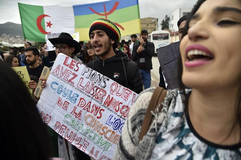 Protesters carry the Algerian flag (L) and the Berber colours side by side at a rally in March against veteran president Abdelaziz Bouteflika in the city of Bejaia east of the capital Algiers