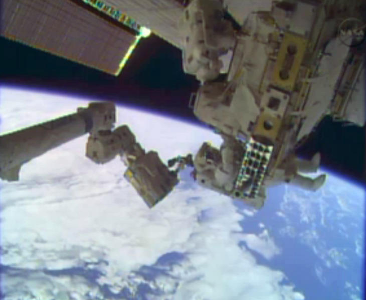 In this image taken from video provided by NASA, astronauts Rick Mastracchio, top, and Michael Hopkins work to repair an external cooling line on the International Space Station on Tuesday, Dec. 24, 2013, 260 miles above Earth. The external cooling line — one of two — shut down Dec. 11. The six-man crew had to turn off all nonessential equipment, including experiments. (AP Photo/NASA)