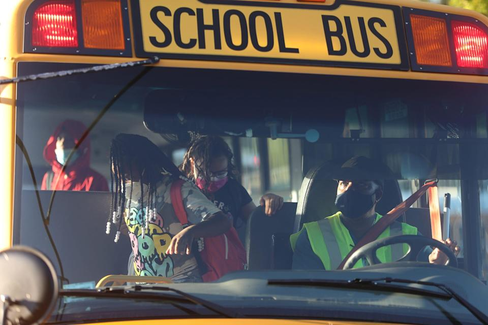 A driver watches as kids depart the school bus in Rochester, New York, on Sept. 9.