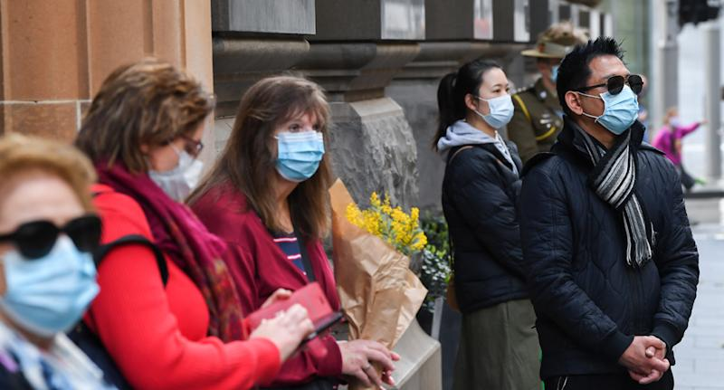 Photo shows people in Sydney wearing face masks.