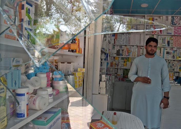 <p>An Afghan shopkeeper looks at broken glass at the site of a suicide attack outside a bank near the US embassy in Kabul on Aug. 29, 2017. (Photo: Shah Marai/AFP/Getty Images) </p>