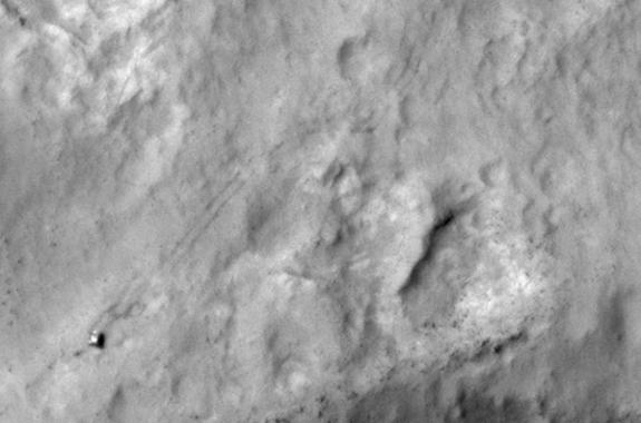 NASA's Curiosity Mars rover and tracks left by its driving appear in this portion of a Dec. 11, 2013, observation by the High Resolution Imaging Science Experiment (HiRISE) camera on NASA's Mars Reconnaissance Orbiter. The rover is near the low