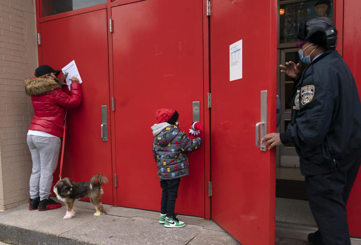 Sheila Melendez, left, completes a form granting permission for random COVID-19 testing for students as she arrives with her daughter Jayceon, center, at P.S. 134 Henrietta Szold Elementary School, Monday, Dec. 7, 2020, in New York. Public schools reopened for in-school learning Monday after being closed since mid-November. (AP Photo/Mark Lennihan)