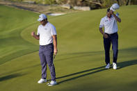 Jon Rahm, of Spain, left, reacts after making a birdie putt on the second sudden-death playoff hole to beat Ryan Palmer, right, during a third round match at the Dell Technologies Match Play Championship golf tournament Friday, March 26, 2021, in Austin, Texas. (AP Photo/David J. Phillip)