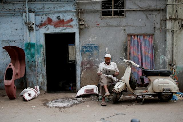 <p>Amin, who paints repaired Vespa scooter parts, reads a newspaper outside his workshop in Karachi, Pakistan Feb. 28, 2018. (Photo: Akhtar Soomro/Reuters) </p>