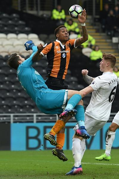 Hull City's Abel Hernandez (C) vies with Swansea City's Lukasz Fabianski and Alfie Mawson (R) during their English Premier League football match on March 11, 2017