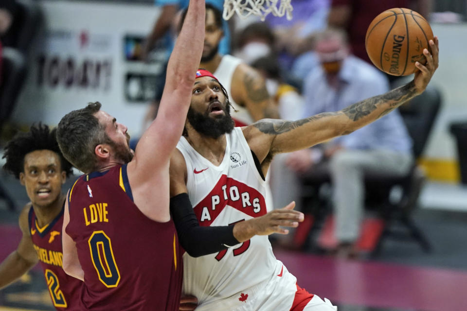 Toronto Raptors' DeAndre' Bembry, right, drives to the basket against Cleveland Cavaliers' Kevin Love in the second half of an NBA basketball game, Saturday, April 10, 2021, in Cleveland. (AP Photo/Tony Dejak)