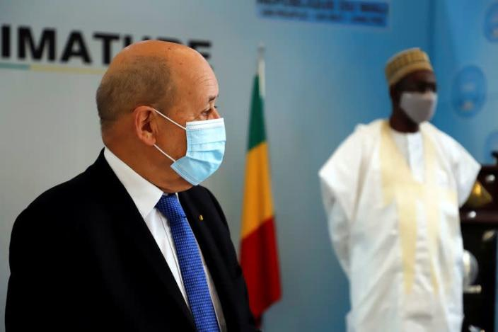 French Foreign Minister Jean Yves Le Drian speaks to journalist as Malian Prime Minister Moctar Ouane listens in Bamako