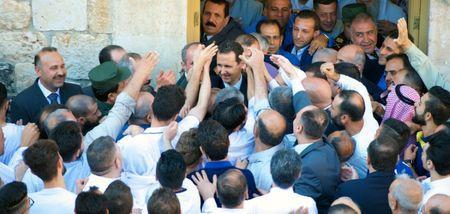 Syria's President Bashar al-Assad greets his supporters during Eid al-Fitr prayers at a mosque in Hama, in this handout picture provided by SANA on June 25, 2017, Syria. SANA/Handout via REUTERS