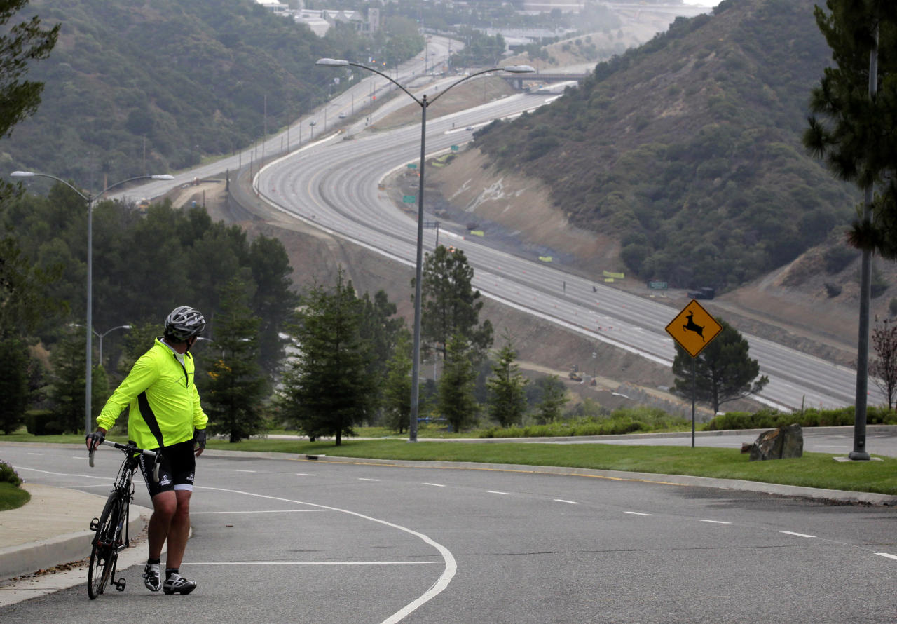 Jerry Wenker watches Interstate 405 during the freeway closure in Los Angeles, Saturday, July 16, 2011. The 10-mile stretch of one of the nation's busiest freeways has turned into a virtual ghost road. (AP Photo/Jae C. Hong)