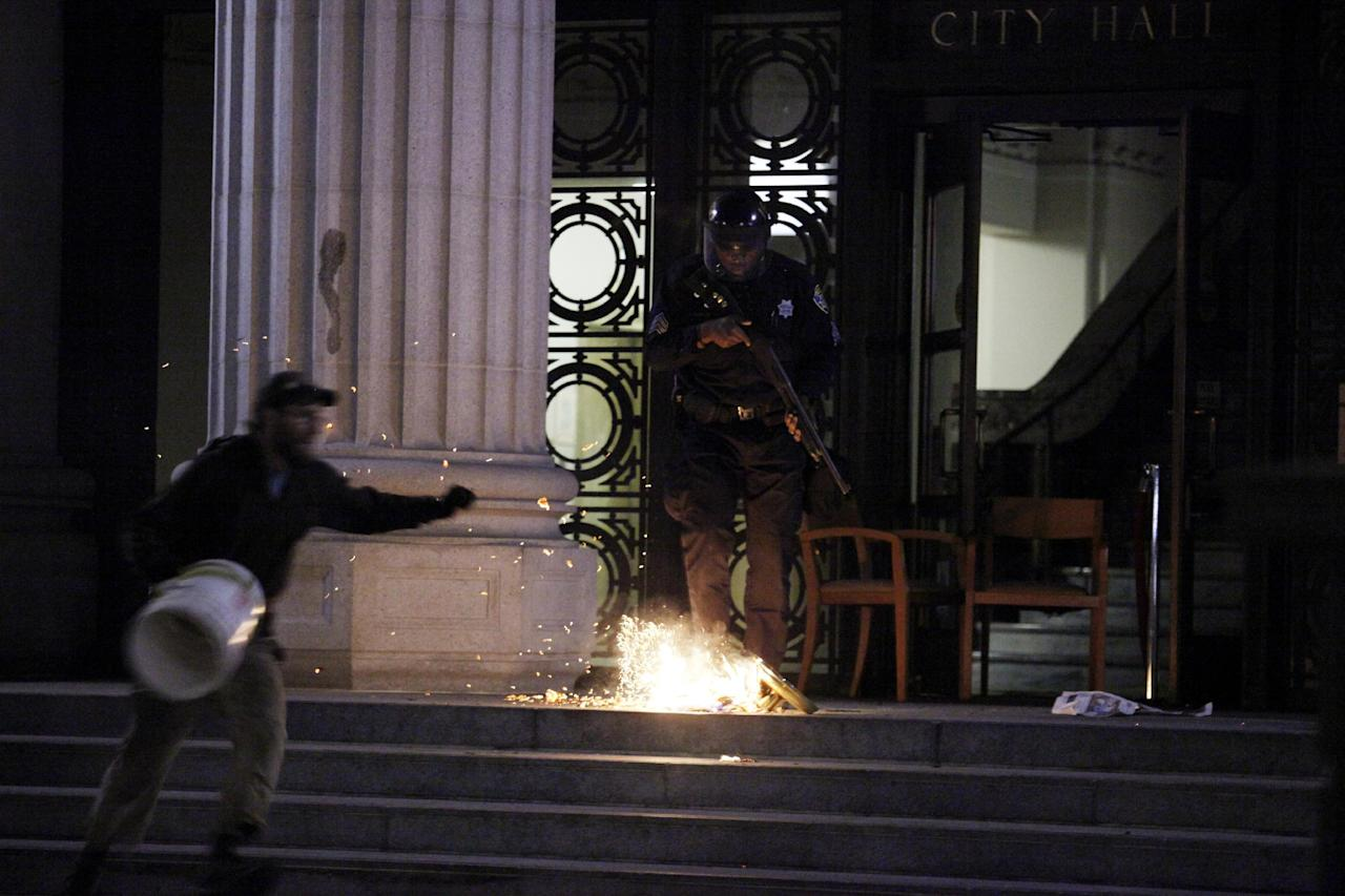 An Oakland City police officer stomps out a burning American flag after Occupy Oakland protestors set City Hall's flag on fire during an Occupy Oakland protest, Saturday, Jan. 28, 2012, in Oakland, Calif. (AP Photo/Beck Diefenbach)