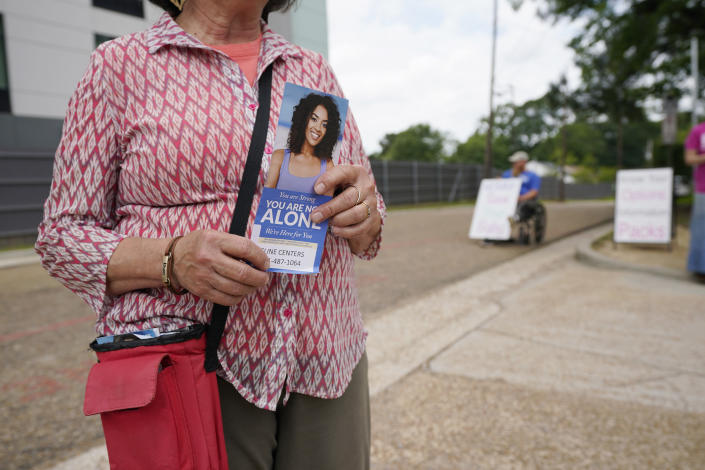 Pam Miller, a anti-abortion sidewalk counselor, prepares to hand out an information packet to any person entering the Jackson Women's Health Organization clinic, Thursday, May 20, 2021, in Jackson, Miss. The clinic is Mississippi's only state licensed abortion facility. On May 17, 2021, the U.S. Supreme Court agreed to take up the dispute over a Mississippi ban on abortions after 15 weeks of pregnancy. The issue is the first test of limits on abortion access to go before the conservative majority high court. Their decision could mean more restrictions, and focuses on the landmark 1973 ruling in Roe v. Wade, which established a woman's right to an abortion. (AP Photo/Rogelio V. Solis)