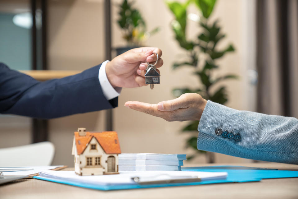 Estate agent giving house keys to woman and sign agreement in office