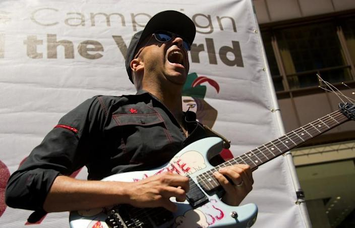 """Former Rage Against the Machine guitarist Tom Morello (C) performs at the National Nurses United rally in Chicago, Illinois, May 18, 2012 ahead of the NATO 2012 Summit. Morello told a crowd at a nurses rally in downtown Chicago that someone should"""" put those NATO criminals in animal cages and crank Rage Against the Machine 24 hours a day."""" AFP PHOTO/Jim Watson (Photo credit should read JIM WATSON/AFP/GettyImages)"""