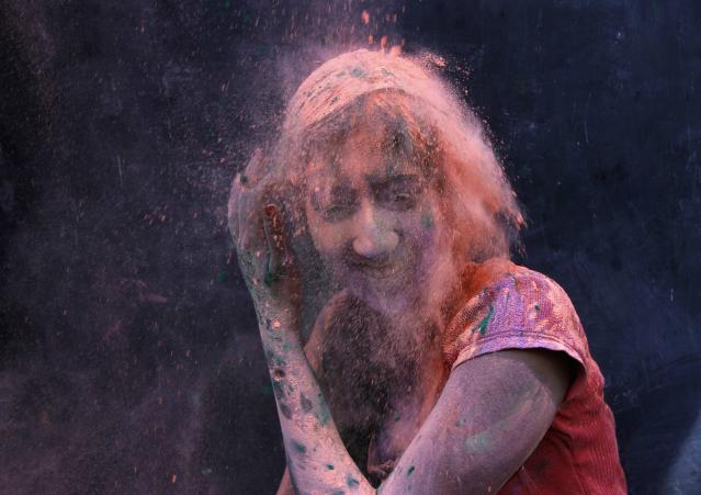 A college student, smeared with colour, smiles as her fellow students pour coloured powder on her during Holi celebrations in the southern Indian city of Chennai March 17, 2014. Holi, also known as the Festival of Colours, heralds the beginning of spring and is celebrated all over India. REUTERS/Babu (INDIA - Tags: SOCIETY RELIGION)