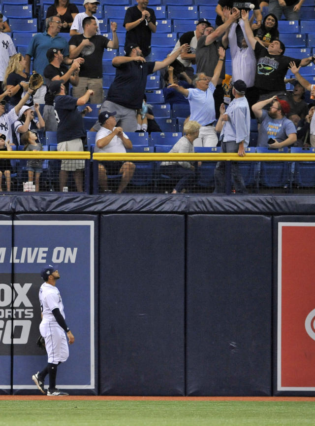 Tampa Bay Rays left fielder Tommy Pham watches as fans reach for a three-run homer run hit by New York Yankees' Gary Sanchez during the third inning of a baseball game Tuesday, Sept. 25, 2018, in St. Petersburg, Fla. (AP Photo/Steve Nesius)