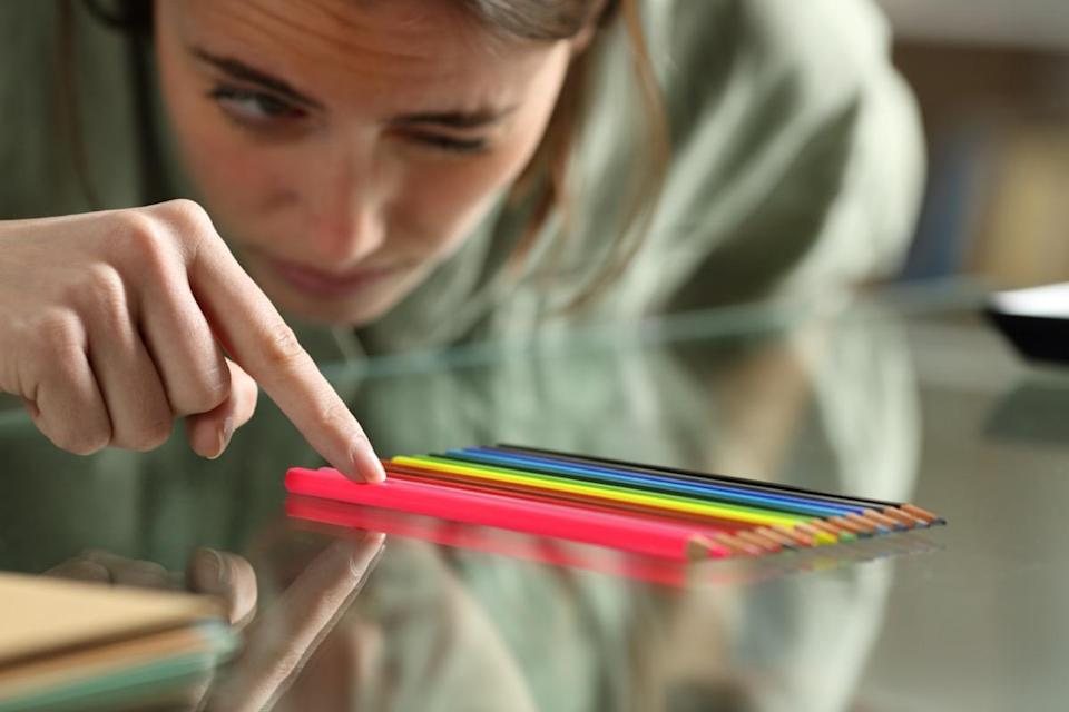 Woman aligning up pencils accurately on a glass table