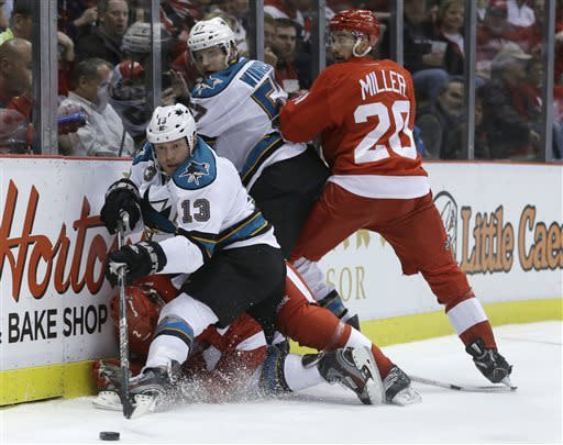 San Jose Sharks left wing Raffi Torres (13) tries controlling the puck as he falls onto Detroit Red Wings defenseman Brendan Smith (2) during the first period of an NHL hockey game in Detroit, Thursday, April 11, 2013. In the background are Red Wings left wing Drew Miller (20) and Sharks center Tommy Wingels (57). (AP Photo/Carlos Osorio)
