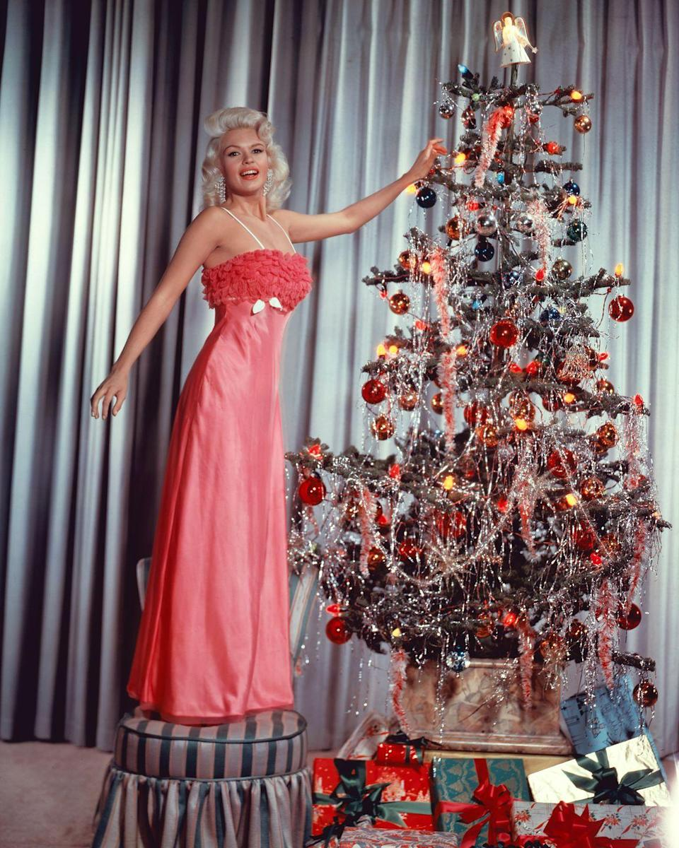 <p>The actress/model puts finishing touches on a colorful holiday tree, circa 1960.</p>