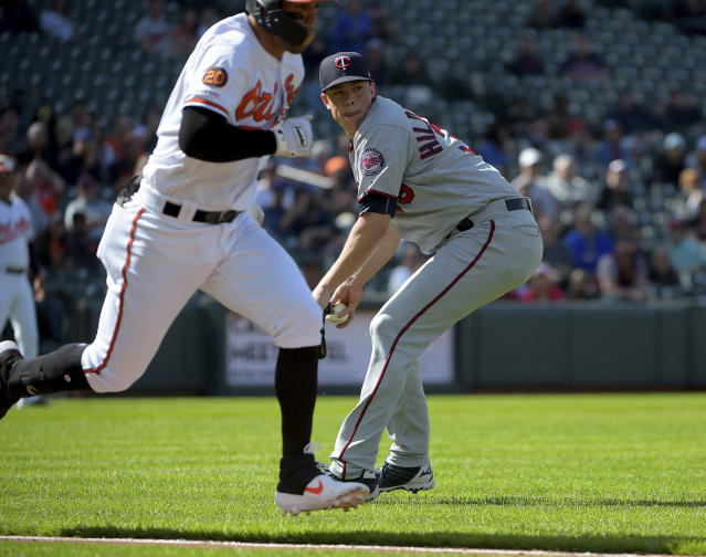 Minnesota Twins relief pitcher Trevor Hildenberger (39) looks to throw to first base to get out Baltimore Orioles Rio Ruiz (14) in the eighth inning of a baseball game, Sunday, April 21, 2019, in Baltimore. (AP Photo/Will Newton)