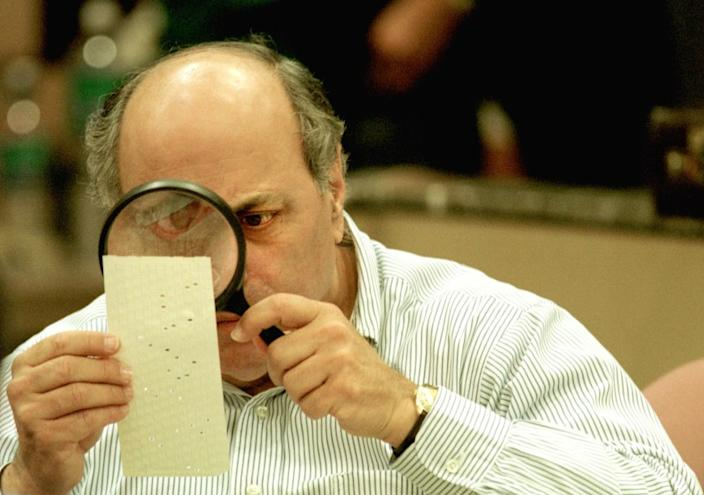 """Judge Robert Rosenberg of the Broward County Canvassing Board uses a magnifying glass to examine a dimpled chad on a punch-card ballot Nov. 24, 2000, during a vote recount in Fort Lauderdale, Fla. <span class=""""copyright"""">(Robert King / Getty Images)</span>"""