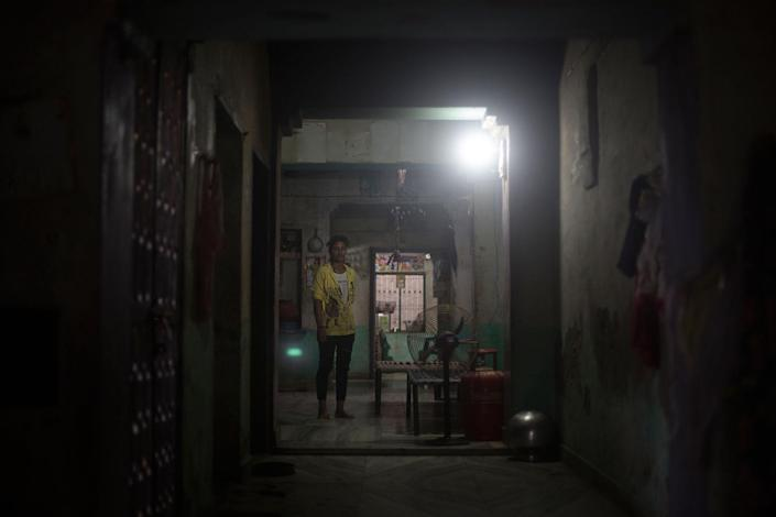"""Ramgani Jat (18) stands in the middle of the main room of her parents' house in Khankla, Bilwara district, Rajasthan, India in July 2016. She was secretly married when she was very young and her marriage became """"effective"""" when she was 14. She fights with her father almost on daily basis because she wants to remain home and keep studying. She walks two hours a day to get to school. (Photo: Rafael Fabrés)"""