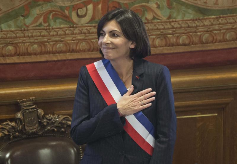 """The new mayor of Paris Anne Hidalgo, wearing the mayoral sash in the color of the French Republic, acknowledges applause after her election, in Paris, Saturday, April 5, 2014. The first woman mayor of Paris has taken office, hailing a """"great advance for all women"""" and saying she feels the weight of responsibility in her new job. (AP Photo/Michel Euler)"""