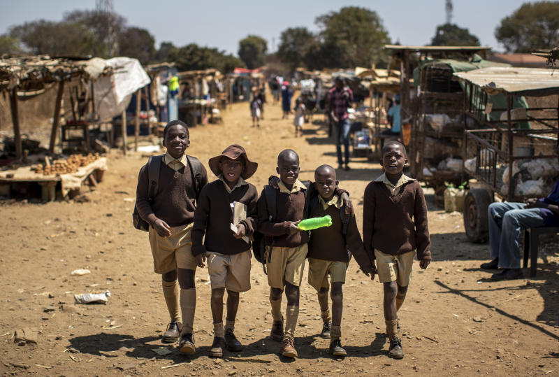 Schoolboys walk back home on the first day of the school term, in Kuwadzana, on the outskirts of the capital Harare, in Zimbabwe Tuesday, Sept. 10, 2019. Former president Robert Mugabe, who enjoyed strong backing from Zimbabwe's people after taking over in 1980 but whose support waned following decades of repression, economic mismanagement and allegations of election-rigging, is expected to be buried on Sunday, state media reported. (AP Photo/Ben Curtis)