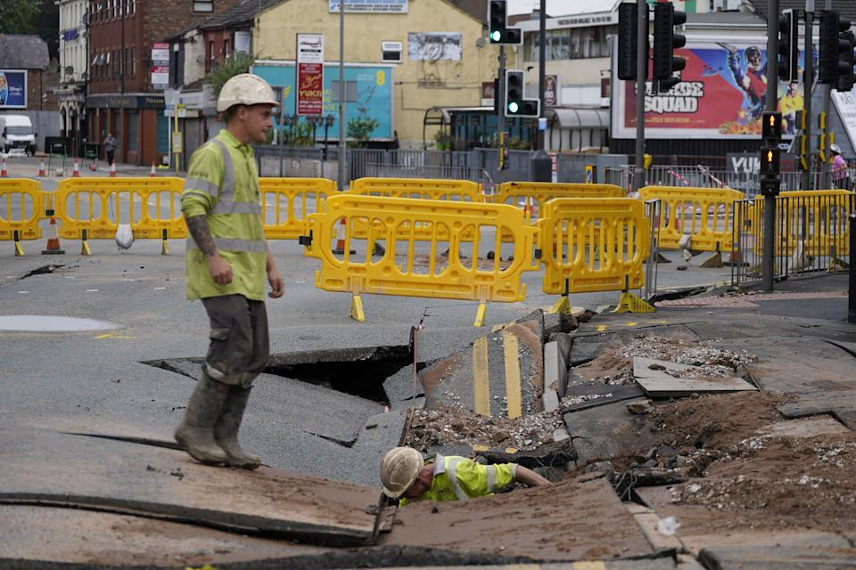 United Utilities workers inspect a 4.5 metre (15ft) by six metre (20ft) sinkhole in Green Lane, Old Swan, Liverpool, caused by a suspected ruptured water main. Picture date: Saturday July 24, 2021.