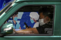 A driver wearing a face mask to help protect from the coronavirus browses his smartphone inside his car against a moral depicting a man receives a COVID-19 vaccine at a vaccination center in Shanghai, China, Friday, Aug. 27, 2021. (AP Photo/Andy Wong)