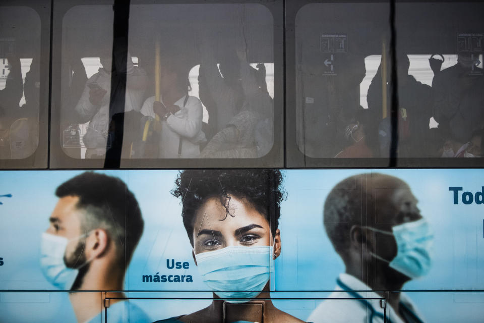 Commuters crowd a bus promoting the use of face masks during the COVID-19 pandemic in Rio de Janeiro, Brazil, Friday, July 23, 2021. (AP Photo/Bruna Prado)