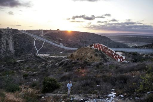 "A painting by foreign and local journalists, which reads ""140 journalists murdered in MX,"" is seen at a US-Mexico border fence in Tijuana"