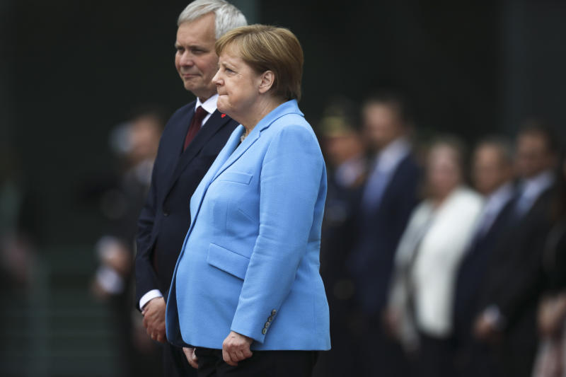 German Chancellor Angela Merkel, right, and Prime Minister of Finland Antti Rinne listen to the national anthems at the chancellery in Berlin, Germany, Wednesday, July 10, 2019. Merkel's body shook visibly as she stood alongside the Finnish prime minister and listen to the national anthems during the welcoming ceremony at the chancellery.(AP Photo/Markus Schreiber)