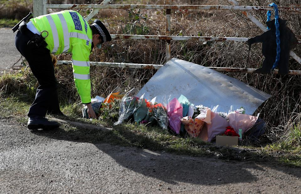A police officer places flowers at the entrance to Great Chart Golf & Leisure Country Club, as the investigation into the disappearance of Sarah Everard continues, in Ashford, Britain, March 12, 2021. REUTERS/Paul Childs
