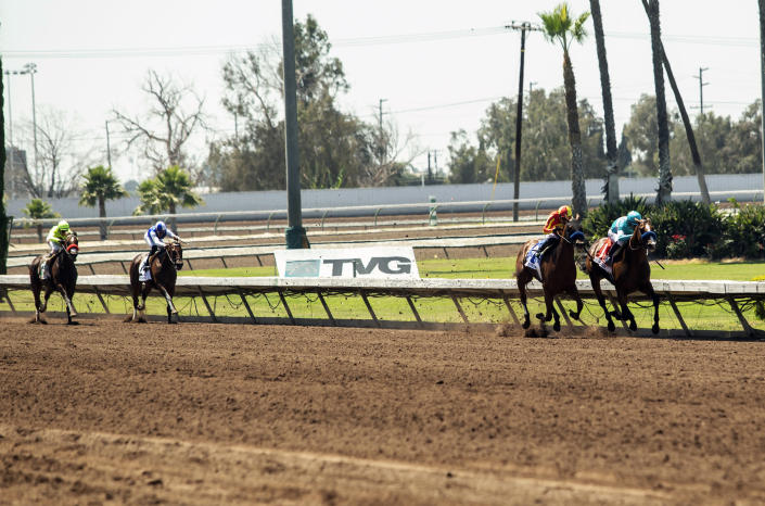 In this photo provided by Benoit Photo, Classier and jockey Mike Smith, far right, hold off stablemate Defunded and jockey Abel Cedillo to win the Grade III $150,000 Los Alamitos Derby horse race, Sunday, July 4, 2021, at Los Alamitos Race Course, in Cypress, Calif. (Benoit Photo via AP)