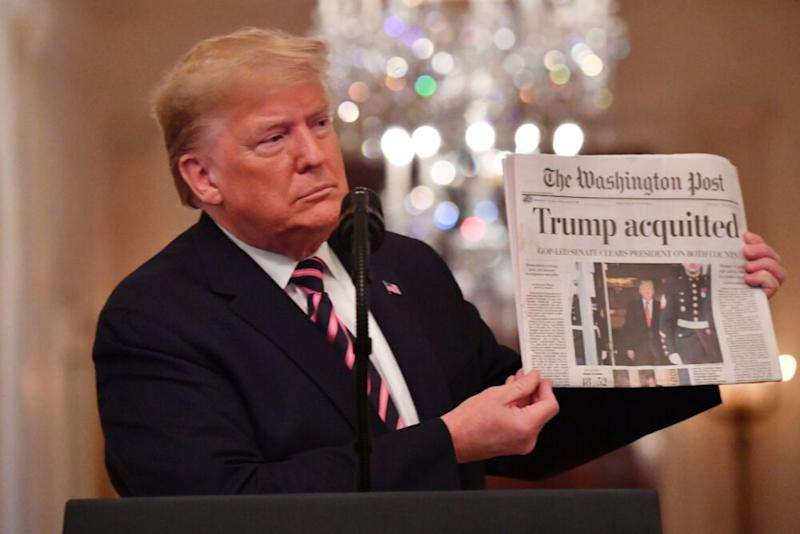 President Donald Trump flaunts a newspaper headlines about his impeachment acquittal during a news conference in the White House earlier this month. | NICHOLAS KAMM/AFP via Getty