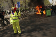 A protestors waves a French flag as a dumpster burns in the background during a yellow vest demonstration in Paris, Saturday, April 20, 2019. French yellow vest protesters are marching anew to remind the government that rebuilding the fire-ravaged Notre Dame Cathedral isn't the only problem the nation needs to solve. (AP Photo/Francisco Seco)