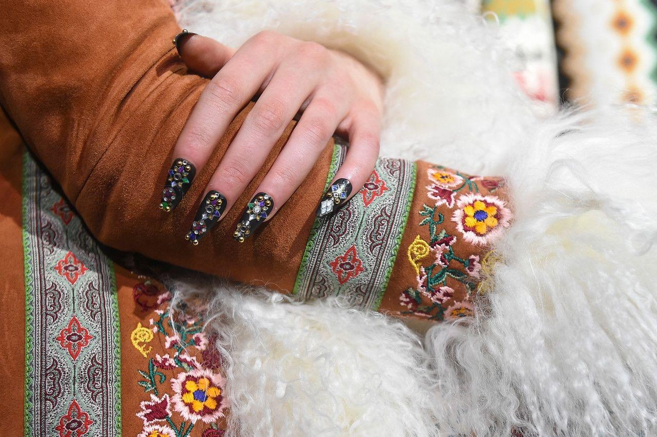 "<p>More is more when it comes to embellishments at Alice & Olivia. The masterminds at KISS chose a coffin nail shape and black polish as a base, adorned with rhinestones and gold jewels. ""I wanted to celebrate the playfulness yet edgy feel of the collection with fierce embellished nails,"" said manicurist Gina Edwards.</p>"